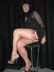 Dark haired leggy crossdresser in a sleek black top and tight skirt