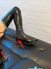 Horny Crossdresser in slutty tight latex masturbates her big cock on leather bed