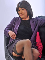 Hot TGirl looking like a sexy secretary, posing on the sofa in black panties and nylons and showing her balls