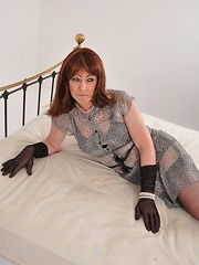 Naughty Tgirl teasing on the bed in gloves, nylons, high heels and black panties