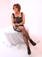 Sexy short haired crossdresser gets a bit frisky having a glass of wine wearing silky nylon stockings