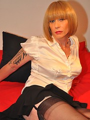 Sexy blonde crossdresser Suzie posing for the camera in a silky blouse, short skirt and hot nylons